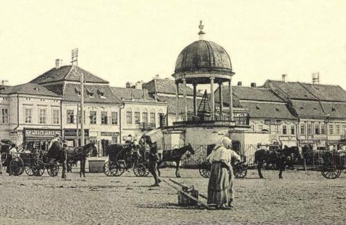 Zenélő kút,Lukács János üzlete,Hints Zoltán gyógyszertára és a régi városházánál Benkő Elek kereskedése,1905k.