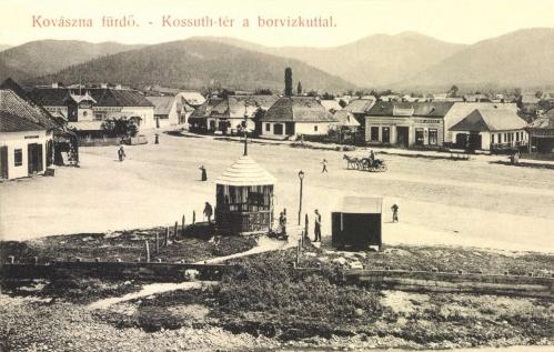 Kovászna:Izsák József üzlete a Kossuth téren a borvíz kúttal.1908.
